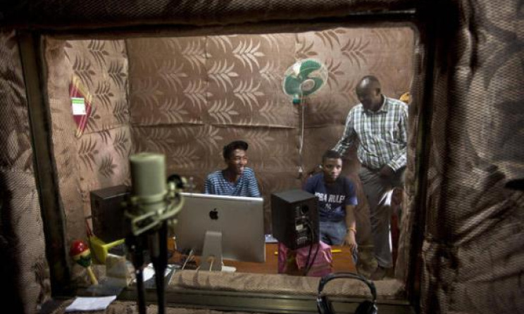 Students talk to school Director Jean Claude Nkulikiyimfura as they practice in the music recording studio Source:www.m.deser
