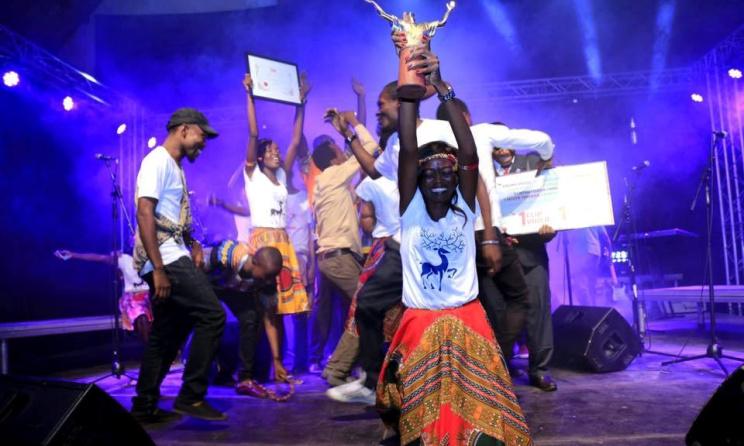 Une chanteuse du groupe brandissant le trophée remis à la finale. Photo: Facebook.