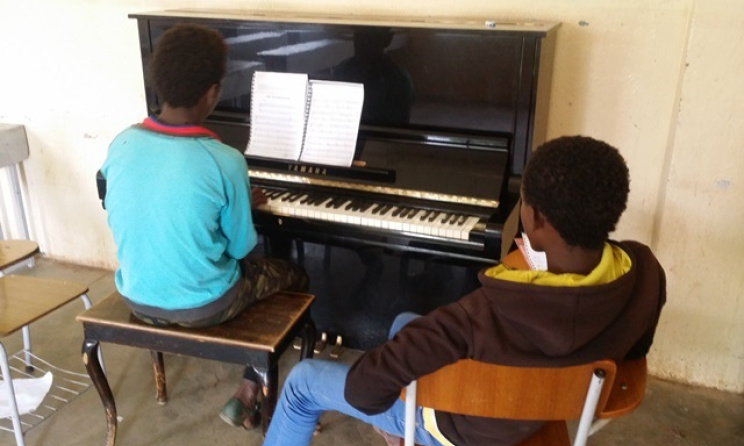 Students during a piano lesson. Photo courtesy of Senai Andemariam
