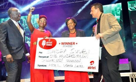 Airtel Uganda COO Diego Javier hands a cheque to Sandra Suubi, local winner of Airtel Trace Music Star, and her family.