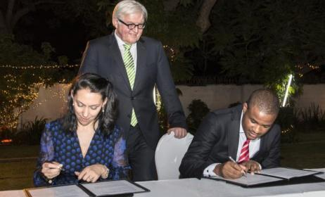 Eddie Hatitye (right) and Nathalie von Siemens (left) sign the MoU as German Foreign Minister Frank-Walter Steinmeier looks on.