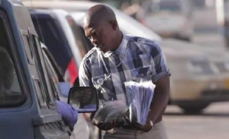 A vendor sells pirated music to motorists on the streets of Harare. Photo: The Herald