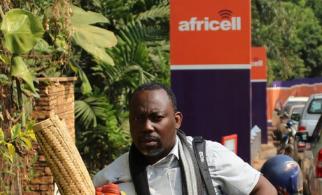 Richard Kawesa who protested in chains, on a mat outside the Africell ofiices. Photo:Chimpreports.com